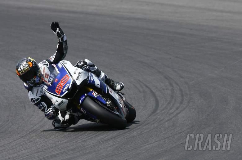 Lorenzo, waving to fans whilst still racing on last lap, Italian MotoGP 2012
