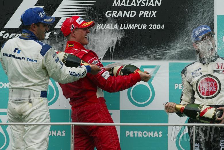 Malaysian GP winner Michael Schumacher [Ferrari] on the podium with Juan Montoya [2nd] and Jenson Bu