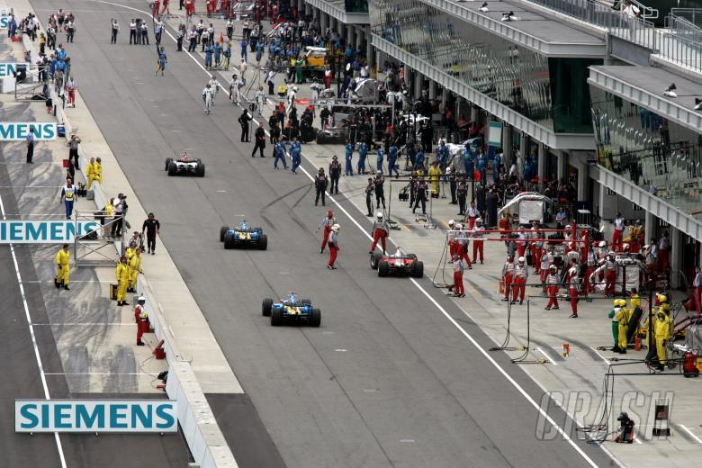 The Michelin teams pull back into their pit garages at the start of the United States Grand Prix