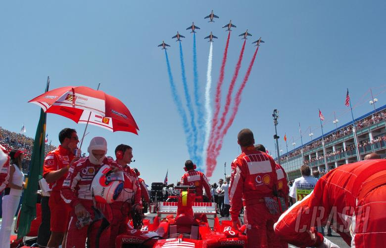 Ferrari mechanics watch as the French airforce flies over the French Grand Prix grid