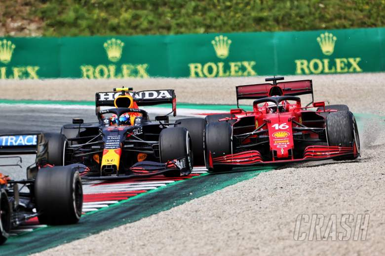 Sergio Perez (MEX) Red Bull Racing RB16B and Charles Leclerc (MON) Ferrari SF-21 battle for position.