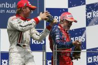 Nico Rosberg helps Heikki Kovalainen celebrate his victory in Sunday`s sprint race at Istanbul Park